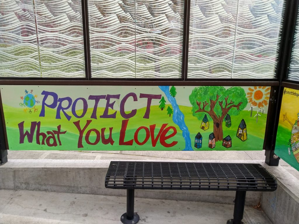 "Image description: The inside of a bus shelter, with a nature scene and the words ""protect what you love"" painted on the back panel"
