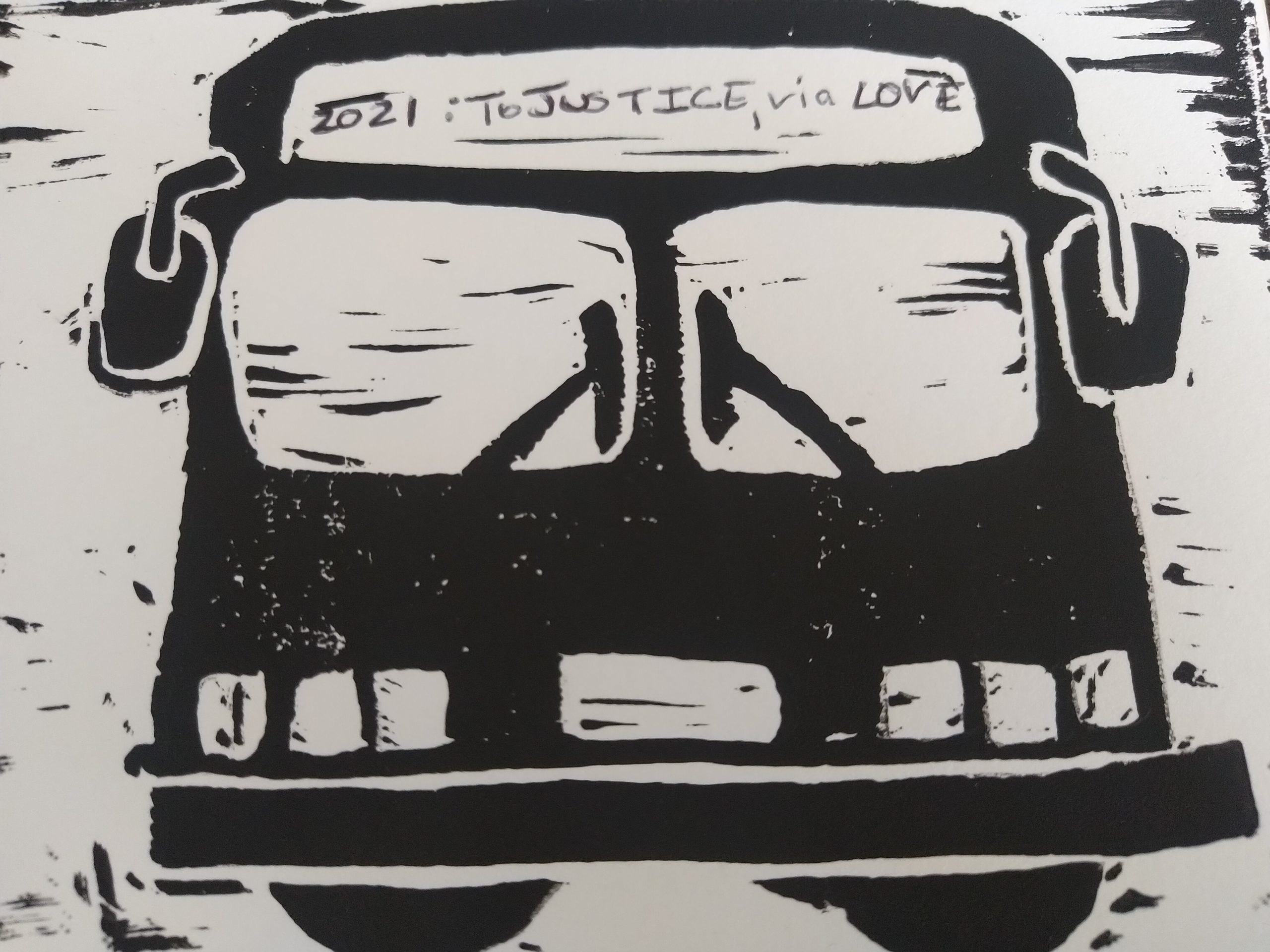 "Image description: A black and white block print of a bus. In the area for the route number and destination is the text, ""2021: To Justice, via LOVE."""