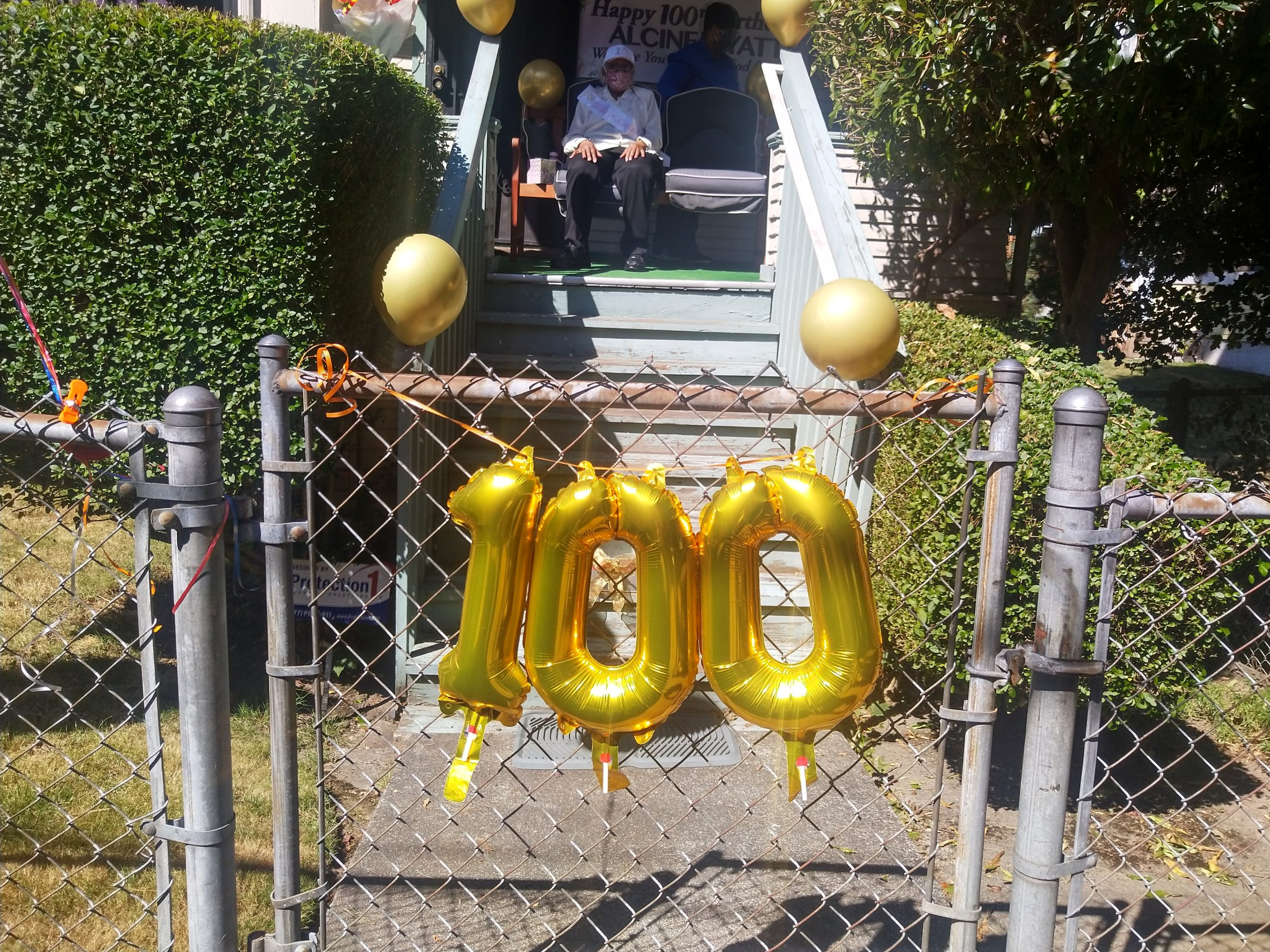Image description: A chain link fence decorate with balloons in the shape of the number 100. Behind the fence is a porch, and on the porch sits an elderly woman wearing a birthday sash.